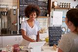 Waitress taking a customerÕs order at till in a coffee shop