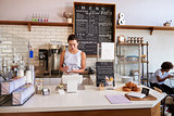 Waitress writing customerÕs order at counter of coffee shop