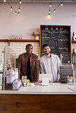 Business partners at the counter of a coffee shop, vertical