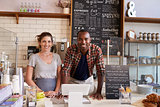 Mixed race couple behind counter at a coffee shop, close up