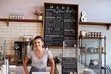 Woman behind the counter of a coffee shop looking to camera