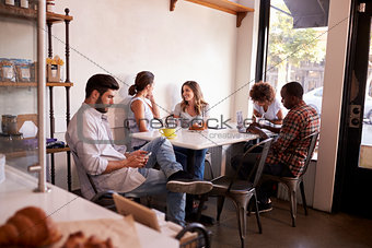Five young adults hanging out at a coffee shop