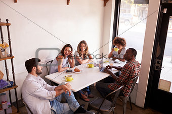 Five adult friends sitting in a cafe, elevated view