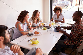 Five adult friends sitting in a cafe, elevated view close up