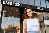 Young woman business owner standing outside cafe shopfront