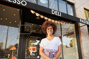 Black female business owner standing outside cafe shopfront