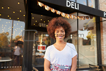 Black female business owner standing in street outside cafe