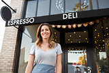 Young white female business owner standing outside cafe