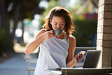 Woman using smartphone and laptop drinking coffee outside