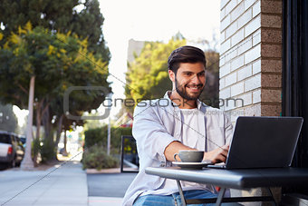 Bearded young man using a laptop at a table outside a cafe