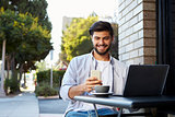 Bearded young man looking at his smartphone outside a cafe