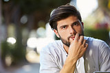 Pensive looking bearded young man sitting outside, portrait