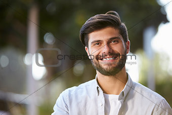 Smiling bearded young man sitting outside, portrait