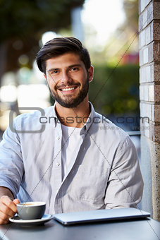 Bearded young man with laptop sitting outside cafe, vertical