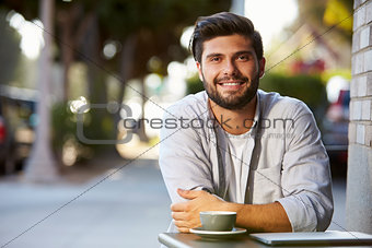 Bearded adult man with laptop sitting at table outside cafe