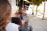 Couple using technology at a table outside a cafe