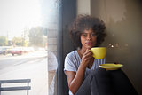 Young black woman sitting beside a window in a cafe