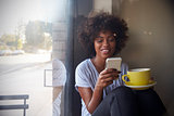 Young black woman using smartphone beside a window in a cafe