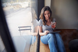 Young woman sits beside window in cafe using tablet computer