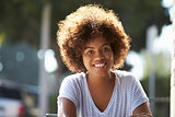 Portrait of happy young black woman sitting outdoors