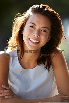 Portrait of young woman sitting outdoors, vertical