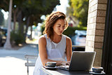 Young white woman using a laptop at a table outside a cafe