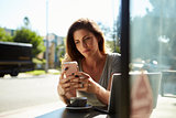 Young white woman using smartphone at a table outside a cafe