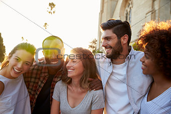 Five happy young adult friends embracing in the street