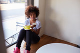 Young black woman sitting by window in cafe using smartphone