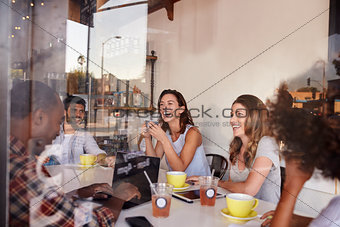 Five young adult friends in a cafe, seen through window