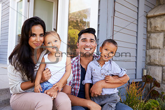 Portrait Of Family Sitting On Steps Outside Home
