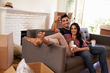 Couple On Sofa Holding Keys Taking A Break On Moving Day