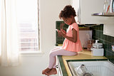 Young Girl Sits In Kitchen And Plays With Mobile Phone