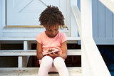 Young Girl Sits On Outdoor Steps Playing With Mobile Phone