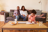 Parents Watch TV As Daughter Colors In Picture Book