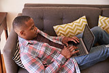 Man Relaxing On Sofa At Home Using Laptop