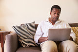 Senior Man Sitting On Sofa At Home Using Laptop