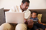 Grandfather And Grandson Sit On Sofa At Home Using Laptop