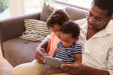 Grandfather And Grandchildren At Home Using Digital Tablet