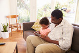 Grandfather And Granddaughter At Home Using Digital Tablet