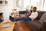 Father And Son Sitting On Sofa At Home Using Digital Tablet