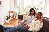 Couple Relaxing On Sofa At Home Using Laptop