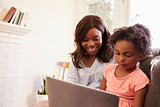 Mother And Daughter Sit On Sofa At Home Using Laptop