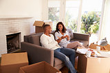 Couple Take A Break On Sofa With Pizza On Moving Day