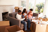 Family Take A Break On Sofa With Pizza On Moving Day