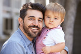 Outdoor Portrait Of Father Holding Son