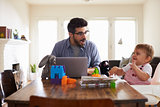 Father Works On Laptop As Baby Son Plays With Toys