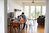 Father Sits At Table And Plays With Baby Son At Home