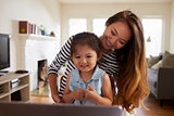 Mother And Daughter Using Laptop At Home Together