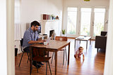 Father Uses Laptop Whilst Baby Son Plays On Floor